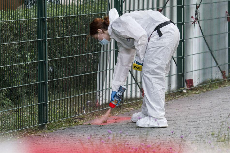Eine Beamtin der Spurensicherung markiert Spuren den Tatort im Stadtteil Gonsenheim, wo ein Mann von der Polizei erschossen wurde.