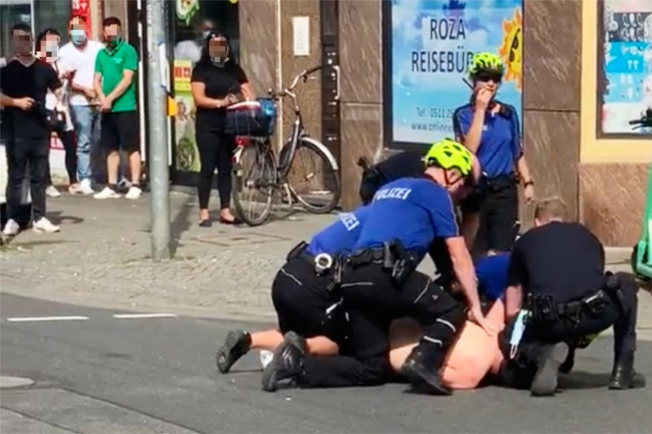 Eine Szene aus dem mittlerweile gelöschten Twitter-Video: Mehrere Polizisten knien auf einem am Boden liegenden Mann und halten ihn fest.