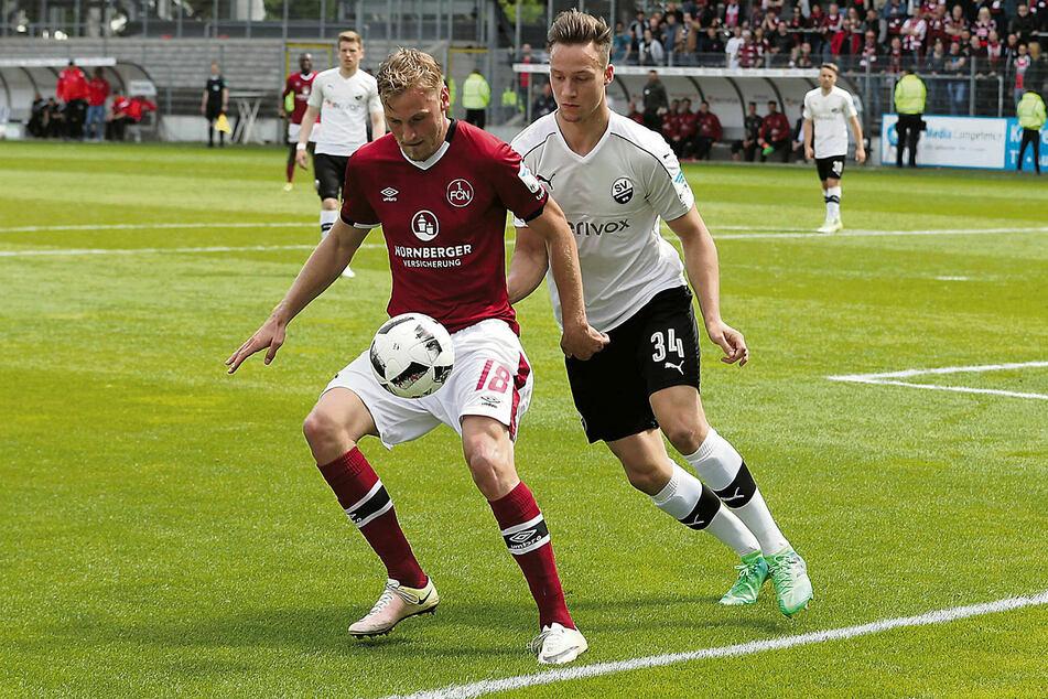 Szene aus dem Spiel, in dessen Nachspielzeit sich Dynamos Neuzugang die böse Verletzung zuzog: Tim Knipping (r.) im Sandhausener Trikot versucht, dem Nürnberger Hanno Behrens den Ball abzuluchsen.