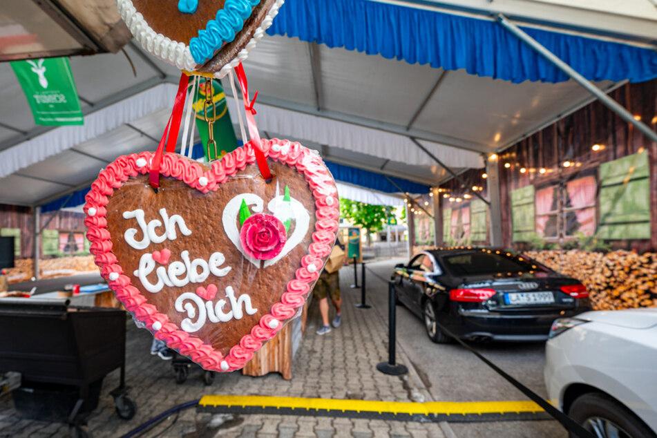 """Ein Lebkuchenherz mit der Aufschrift """"""""Ich liebe Dich"""""""" hängt vor einem Drive-in-Festzelt in Landshut."""