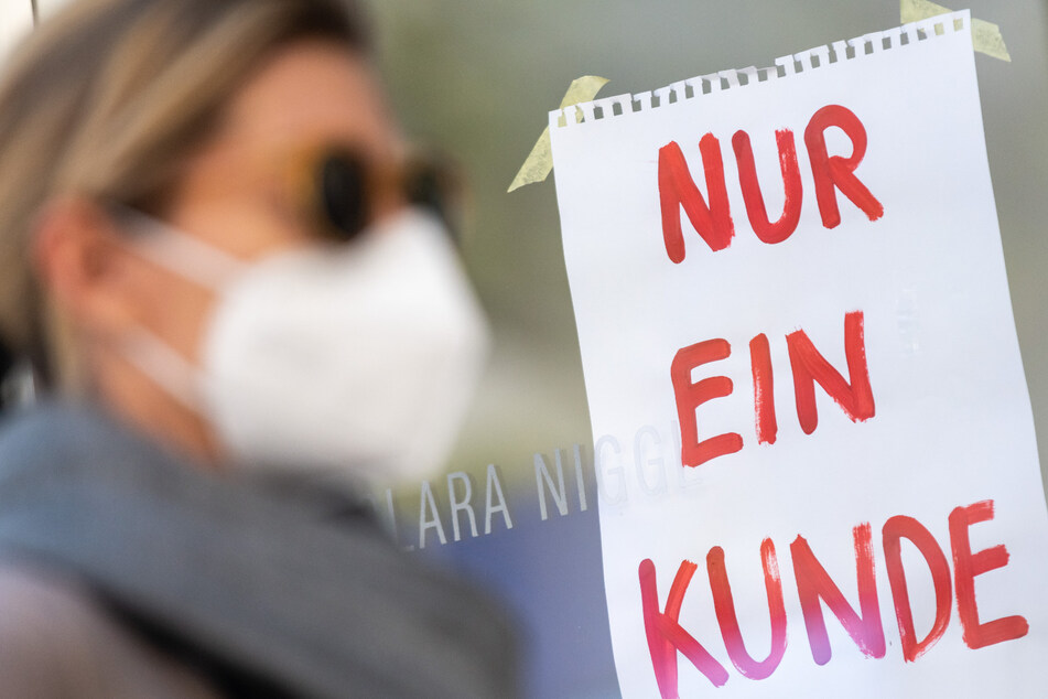 """Eine Frau mit Nase-Mund-Schutzmaske geht an einem Geschäft vorbei, an dem ein Schild mit der Aufschrift """"Nur ein Kunde"""" angebracht ist. (Archivbild)"""