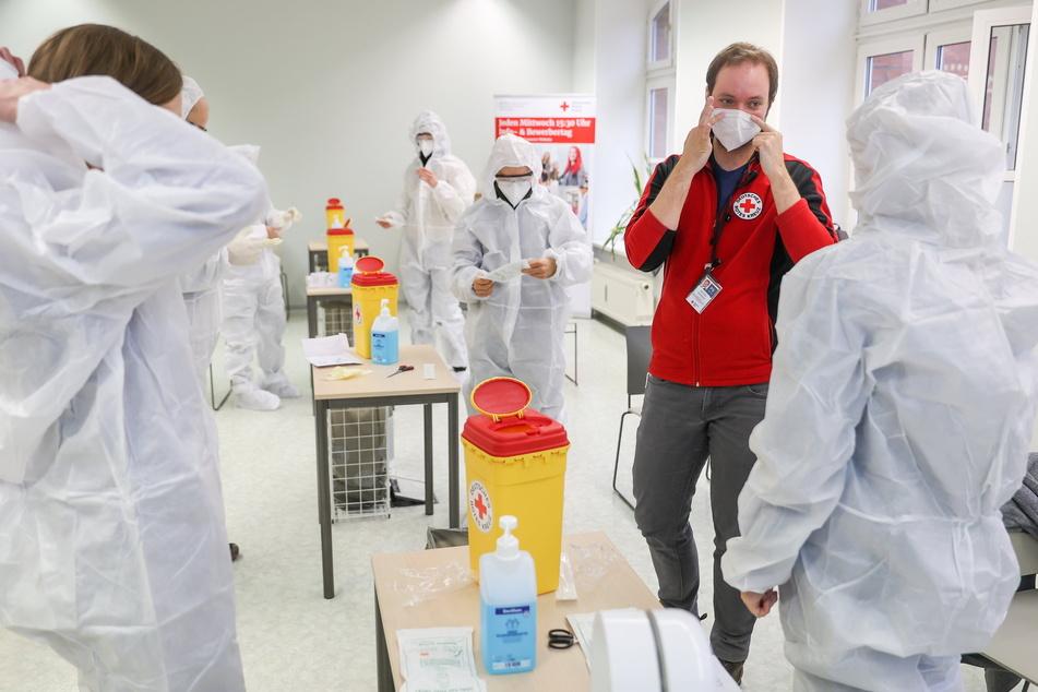 DRK-Dozent Jascha Gionkar erläutert den Teilnehmern des Schnelltester-Kurses in Leipzig das richtige Anlegen der Schutzausrüstung.