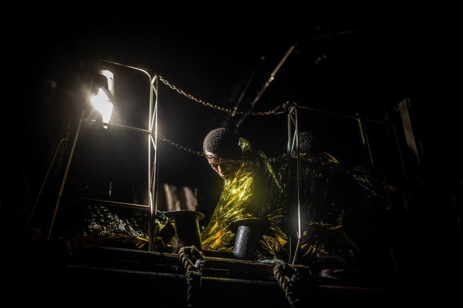 """Ein in eine Thermodecke gewickelter Mann ruht an Bord des Rettungsschiffes """"Louise Michel"""" aus, nachdem er aus einem überfüllten Schlauchboot gerettet wurde"""