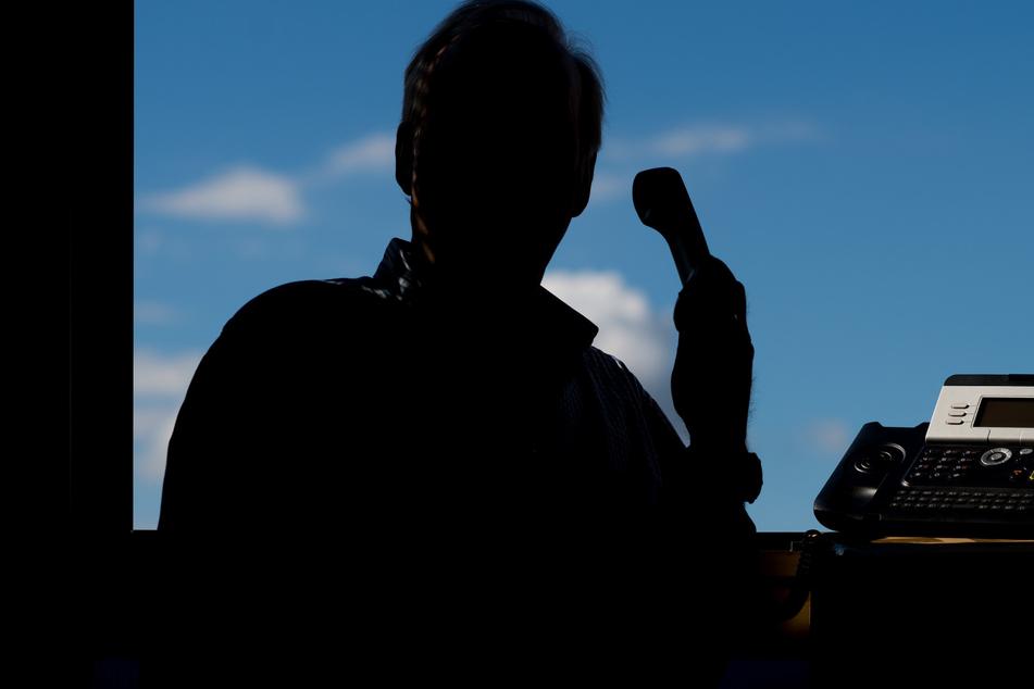 Ein Mann hält ein Telefon. (Illustration)