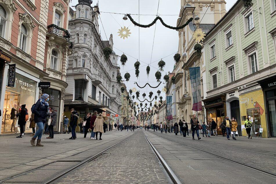 Menschen mit Mund-Nasen-Schutz gehen in der Vorweihnachtszeit in der recht leeren Innenstadt an Geschäften vorbei. Österreich geht ab dem 26. Dezember für mindestens drei Wochen erneut in den coronabedingten Lockdown.