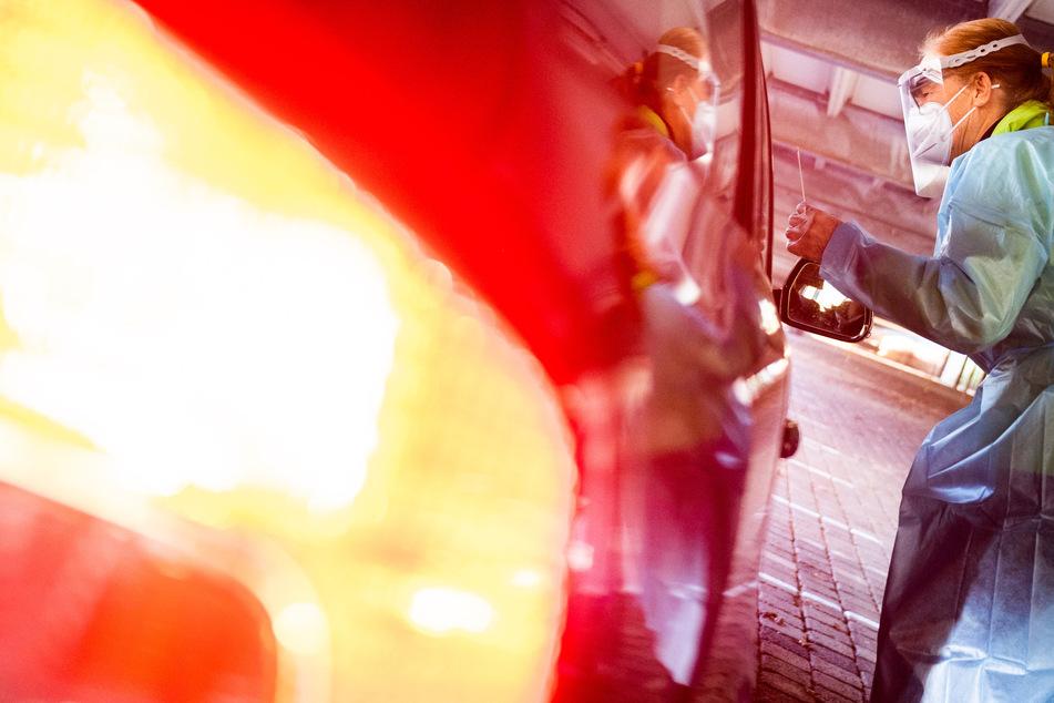 Eine Helferin testet Insassen eines Autos in einem Testzentrum.