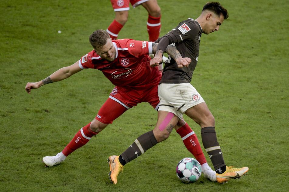 Fortuna-Knipser Rouwen Hennings (l.) und FC St. Paulis Rodrigo Zalazar kämpfen um den Ball.