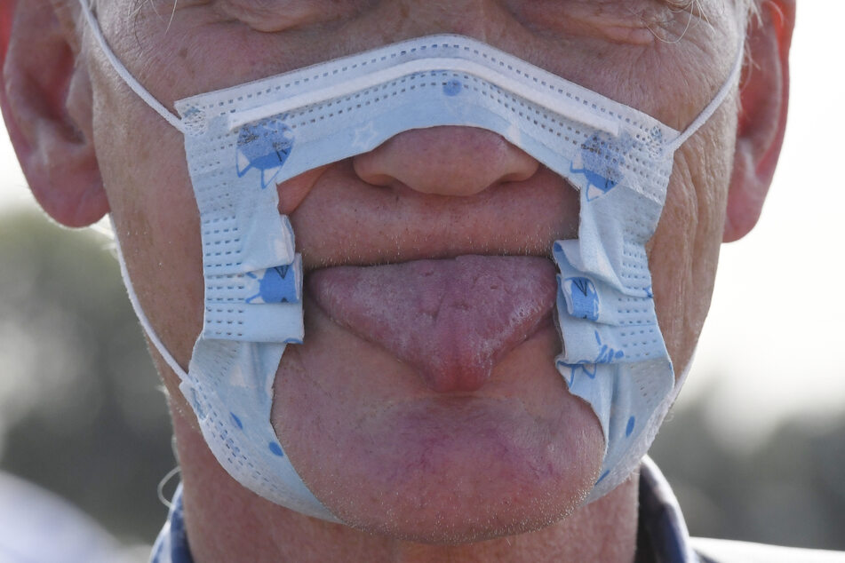 Ein Teilnehmer einer Demonstration protestiert auf den Rheinwiesen mit einer zerschnittenen Maske und herausgestreckter Zunge gegen die Maßnahmen zur Bekämpfung des Coronavirus.