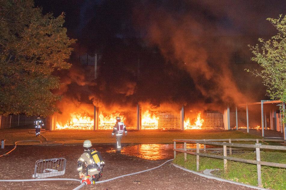Einsatzkräfte kämpfen gegen die Flammen auf dem Schulgelände.