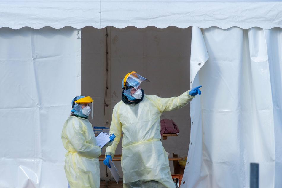 Zwei Helfer in Schutzanzügen vor dem Universitätsklinikum in Magdeburg.