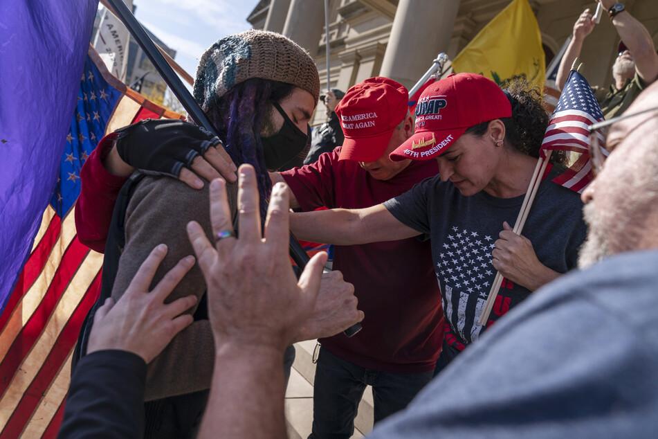 Lansing: Anhänger des US-Präsidenten D. Trump, die gegen die Wahlergebnisse demonstrierten, beten mit einem Gegendemonstranten nach deren Kundgebung.