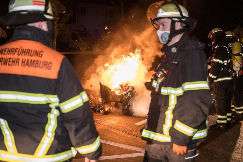 Einsatzkräfte stehen vor einem brennenden Müllcontainer.