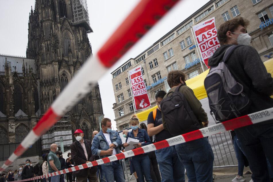 Menschen stehen Schlange bei einer Impfaktion der Stadt Köln vor dem Hauptbahnhof und dem Kölner Dom.