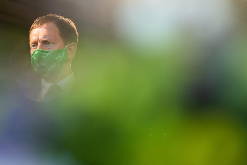 Michael Kretschmer (CDU), Ministerpräsident von Sachsen, steht mit Mundschutz vor der sächsischen Staatskanzlei.