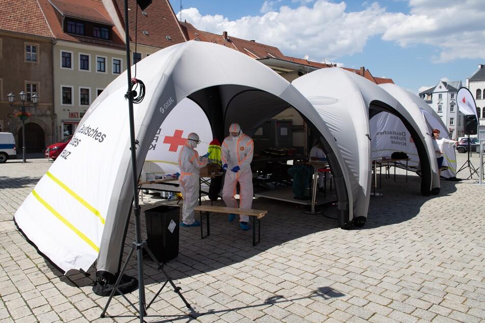 Zwei Mitarbeiter des Deutschen Roten Kreuzes (DRK) in Schutzkleidung stehen in der neuen mobilen Covid-19-Beprobungsstation.