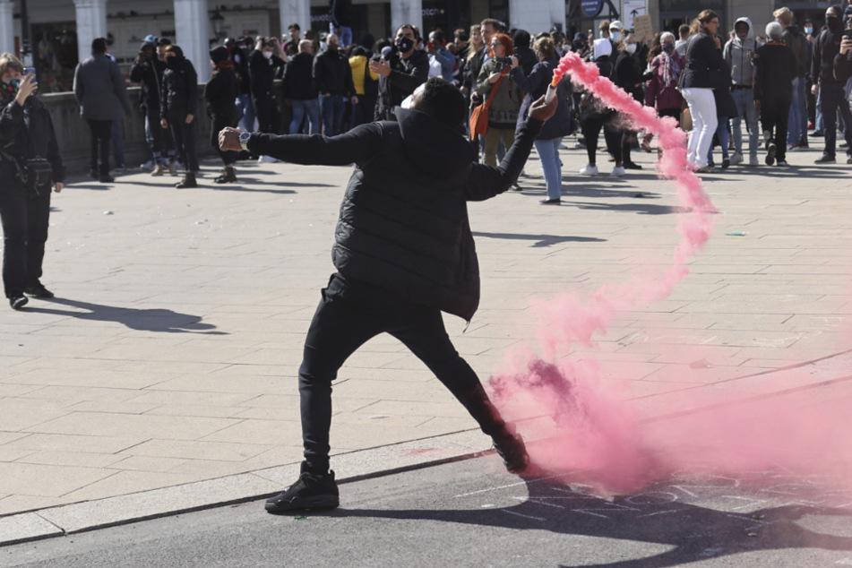 Ein Demonstrant wirft eine Rauchpatrone in Richtung der Polizeikräfte auf einer aufgelösten Demonstration.