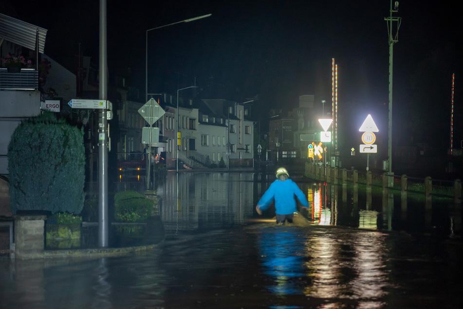 Ein Feuerwehrmann watet in der Nacht durch die von der Kyll überflutete Bahnhofstrasse in Kordel.