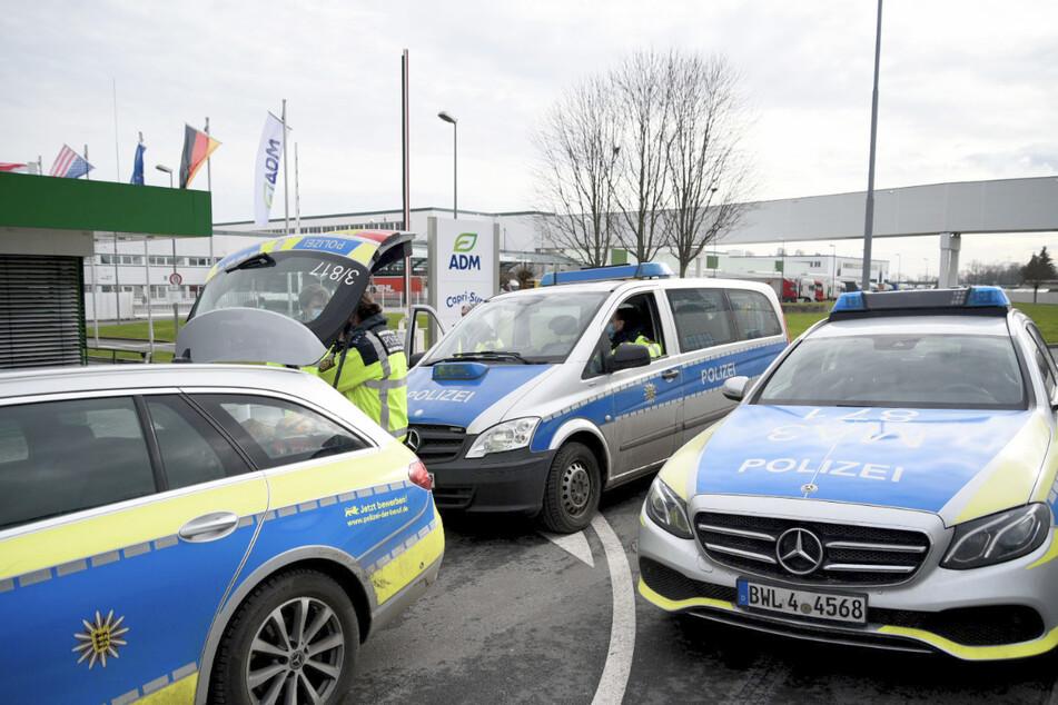 Polizeiautos stehen vor einem Werk eines Getränkeherstellers. Dort hatte eine Serie explosiver Postsendungen begonnen. Nun kommt der Mann vor Gericht.