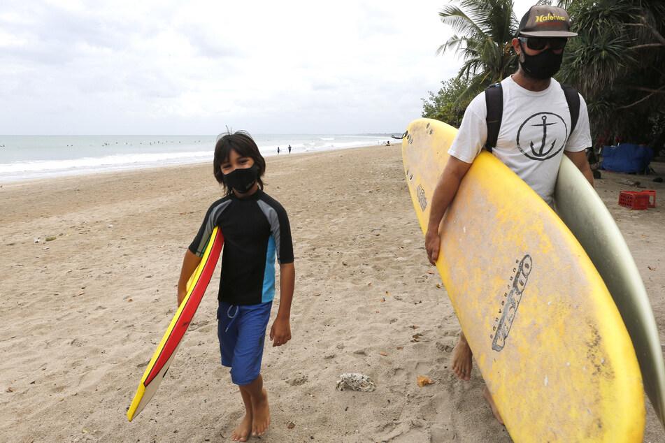 Touristen mit Mundschutz tragen ihre Surfbretter am Strand von Kuta auf Bali.