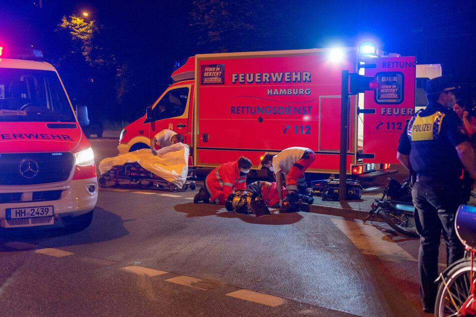 Die alarmierten Rettungskräfte versorgen den am Boden liegenden Radfahrer.