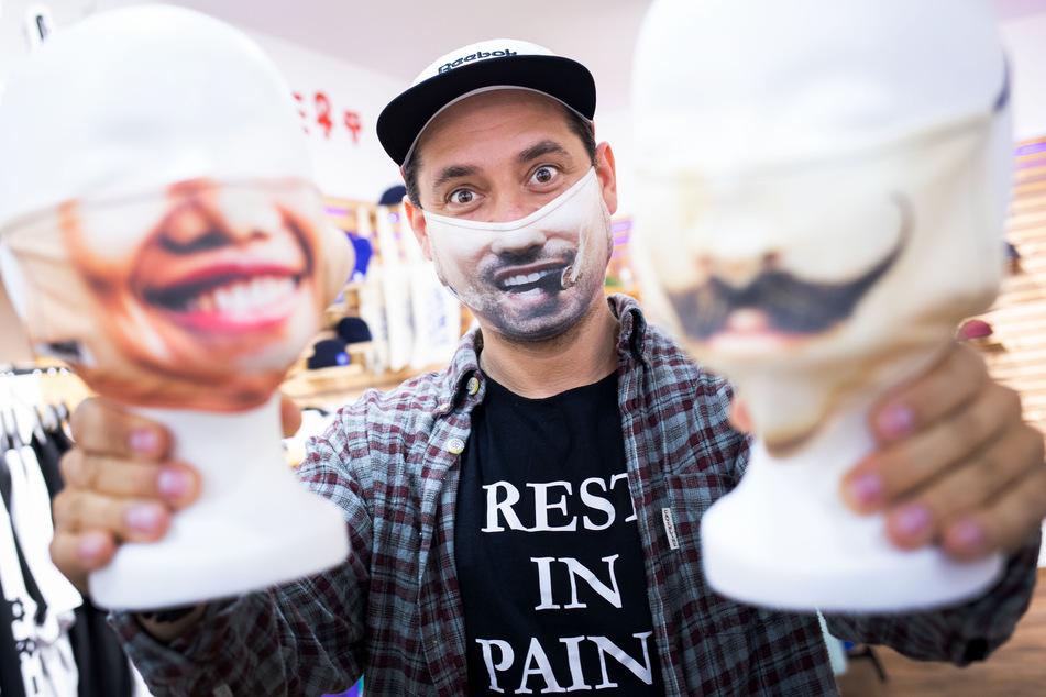 Der Unternehmer zeigt seine individualisierten Foto-Masken.