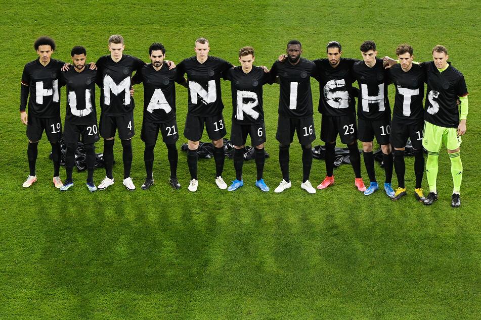 """Die Spieler der deutschen Nationalmannschaft stehen zusammen und bilden den Schriftzug """"Human Rights""""."""