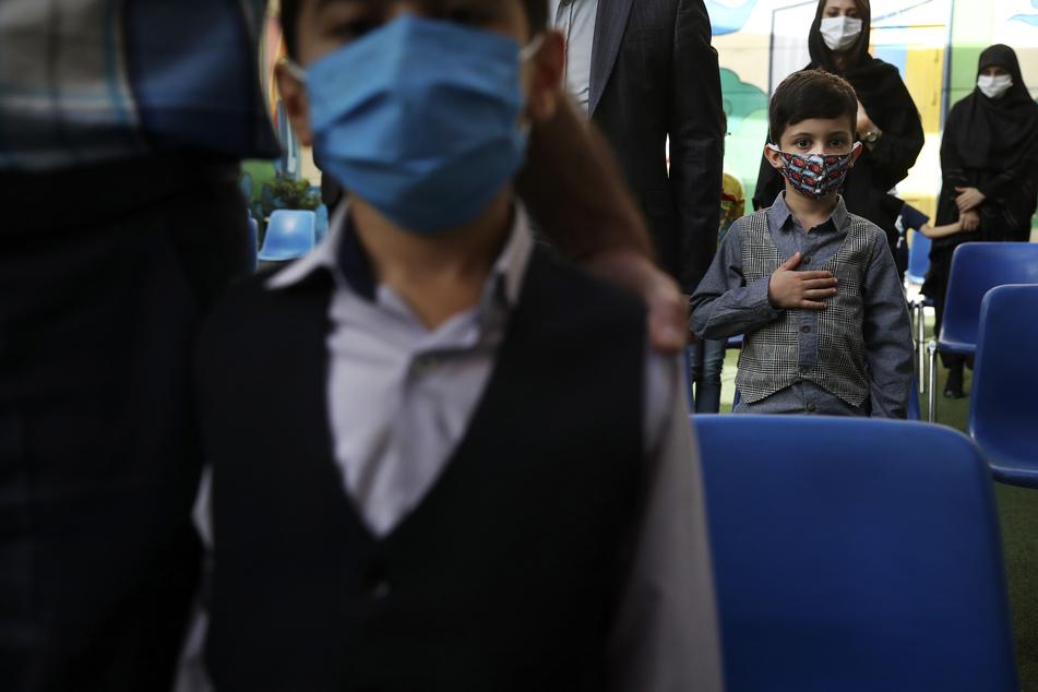 Schüler und ihre Eltern tragen Schutzmasken, um die Verbreitung des Coronavirus zu verhindern und hören die Nationalhymne, während der Eröffnungszeremonie der Hashtroudi-Schule.