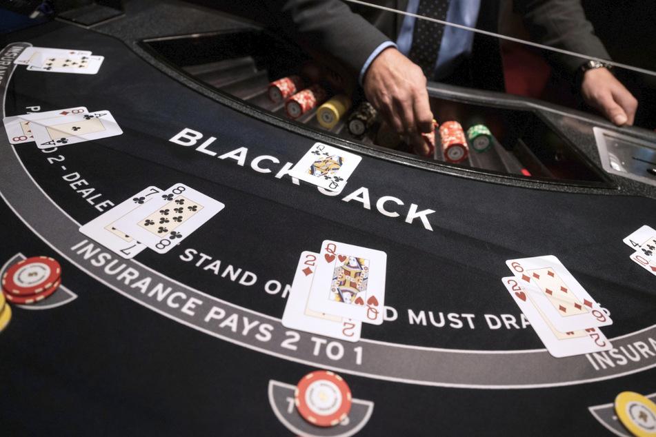 Der Mann hat im Spiel Black Jack den Jackpot geknackt. An der Kasse der Spielbank holte er seinen Gewinn stapelweise ab.