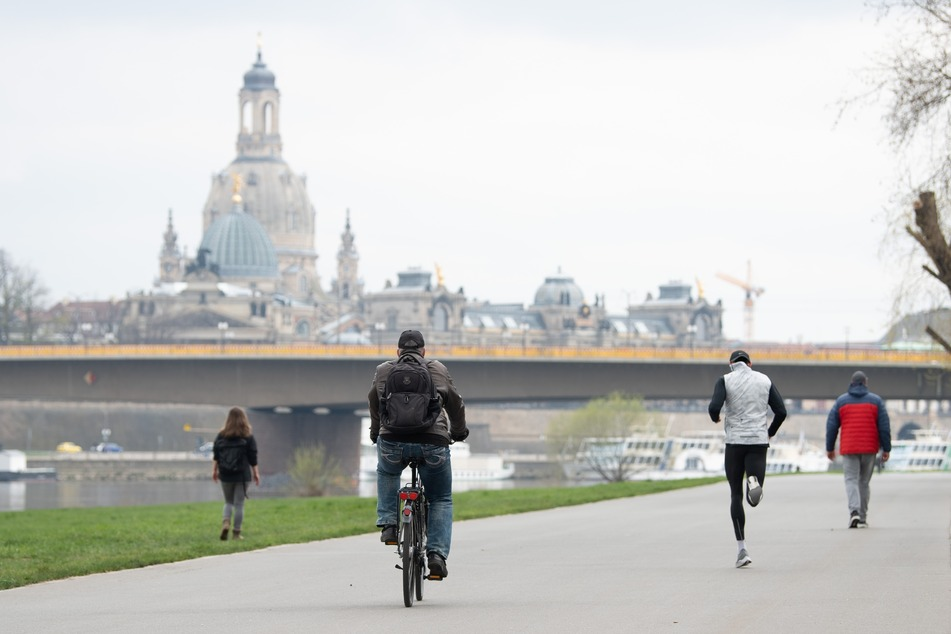 Passanten und Radfahrer am Ufer der Elbe vor der Frauenkirche.