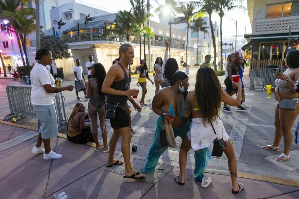 """Eine Gruppe von Touristen tanzt auf dem Ocean Drive in Miami Beach. Die Ausgangssperre könnte bis Ende des """"Spring Break"""" andauern."""