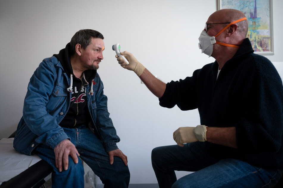 Mediziner Hans-Gerd Schmitz misst in seiner Sprechstunde im Fliednerhaus der Diakonie bei Thorsten Böhme mit einem kontaktlosen Fieberthermometer die Temperatur.