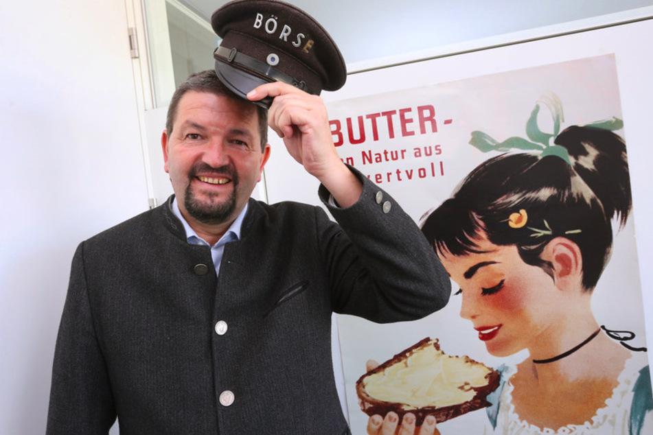 Clemens Rück, Geschäftsführer der Süddeutschen Butter- und Käse-Börse, steht in seinem Büro vor einem alten Werbeplakat.