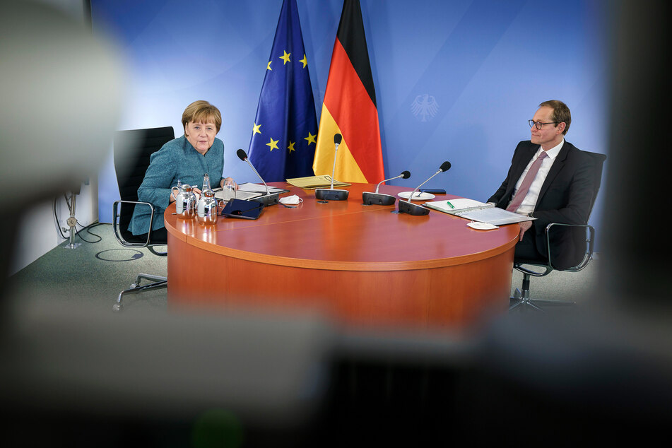 Bundeskanzlerin Angela Merkel (66, CDU, l.) und Michael Müller (56, SPD), Berlins Regierender Bürgermeister, sitzen während des digitalen Impfgipfels mit den Ministerpräsidenten der Länder an einem Tisch,