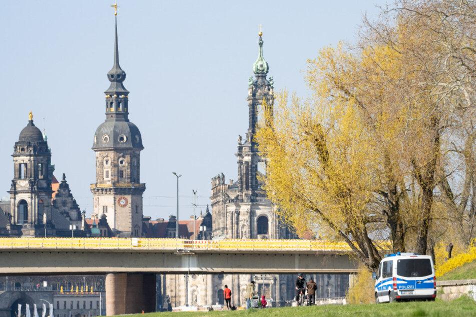 Ein Polizeiwagen fährt am Sonntagmorgen am Dresdner Königsufer entlang, um die Einhaltung der Vorschriften zur Eindämmung des Coronavirus zu kontrollieren.