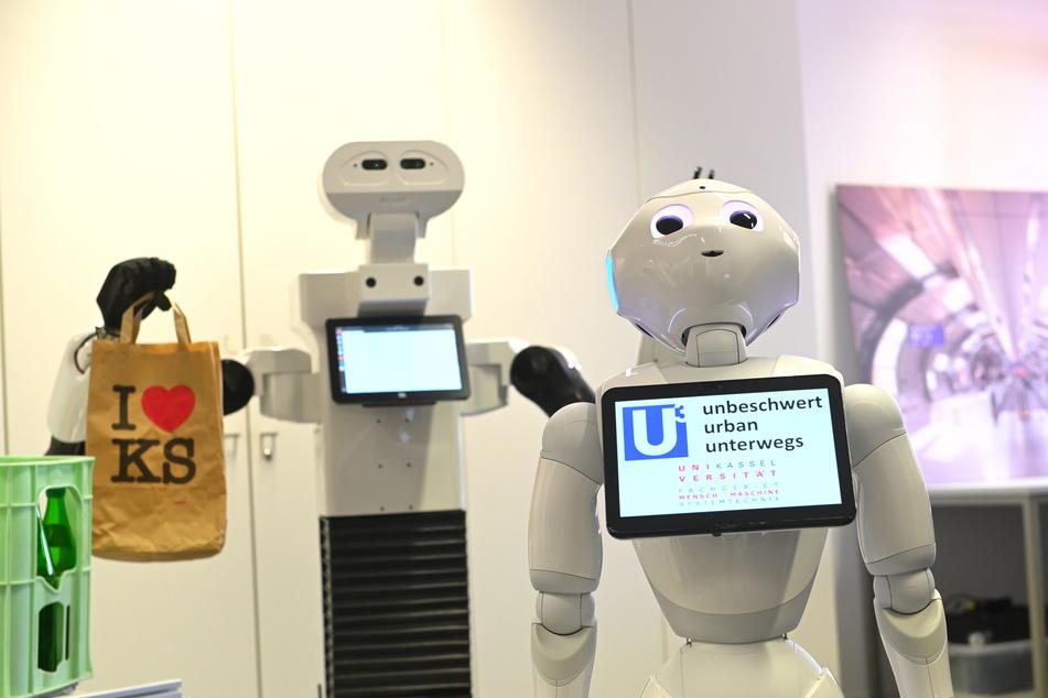 Roboter Pepper (r.) steht vor einem Transportroboter mit Tüte in der Hand.