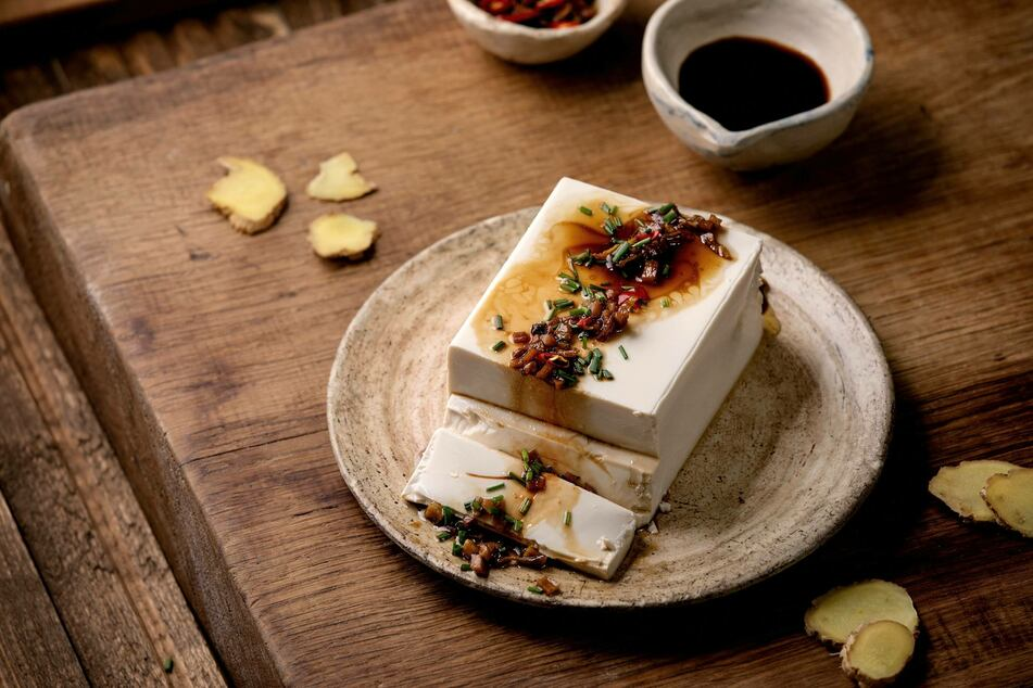 Yum! Silk tofu japanese soy cheese with chili ginger, chive and soy sauce topping on ceramic plate over wooden table.