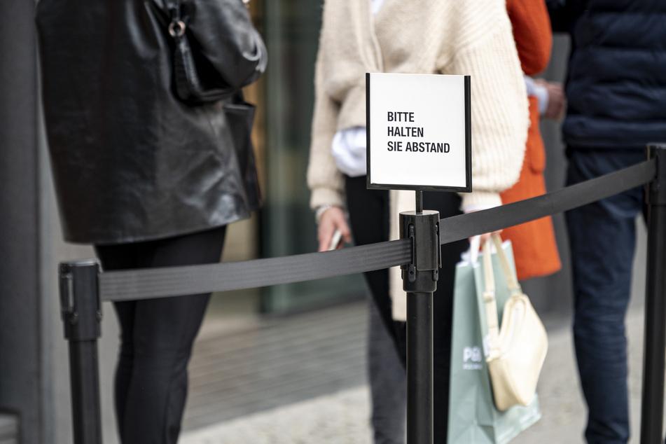 """Neben einer Schlange vor einem Geschäft am Ku'Damm steht ein Hinweisschild mit der Aufschrift """"Bitte halten Sie Abstand"""". Aufgrund der Corona-Pandemie wird ein negativer Corona-Test zum Einkaufen in Geschäften, für Besuche im Friseur- oder Kosmetiksalon, in Museen und Galerien benötigt."""