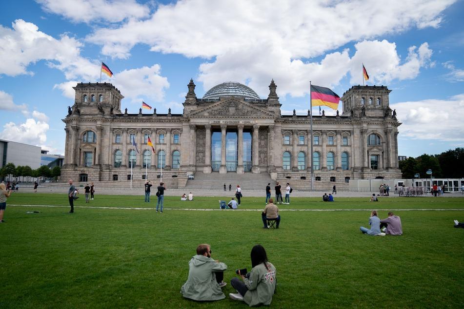 Passanten sitzen auf der Wiese vor dem Reichstagsgebäude.