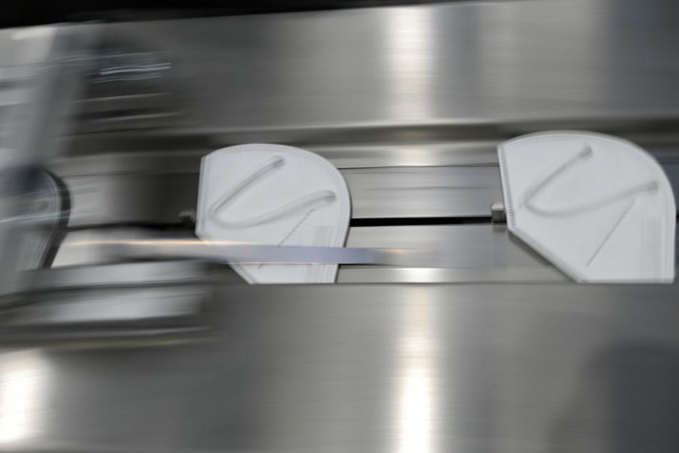 """Gefaltete FFP2-Masken der Marke """"BlueBec"""" werden in einer Werkshalle der Imstec GmbH automatisch zu einer Verpackungsmaschine geschoben."""
