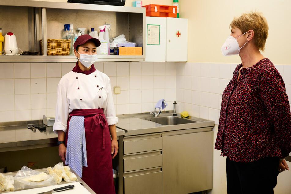 """Elke Breitenbach (60, r.), Senatorin für Integration, Arbeit und Soziales, spricht mit Yagmur, der Auszubildenden in der Küche des Abacus Tierpark Hotel. Das Pilotprojekt """"Ausbildungshotel"""" startete im November 2020 für Azubis, die wegen der Corona-Krise ihre Ausbildung nicht starten oder fortsetzen konnten."""