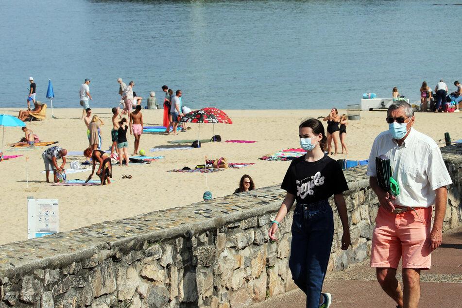 Menschen mit Mund-Nasen-Schutz am Strand in Saint-Jean-de-Luz im Südwesten Frankreichs.