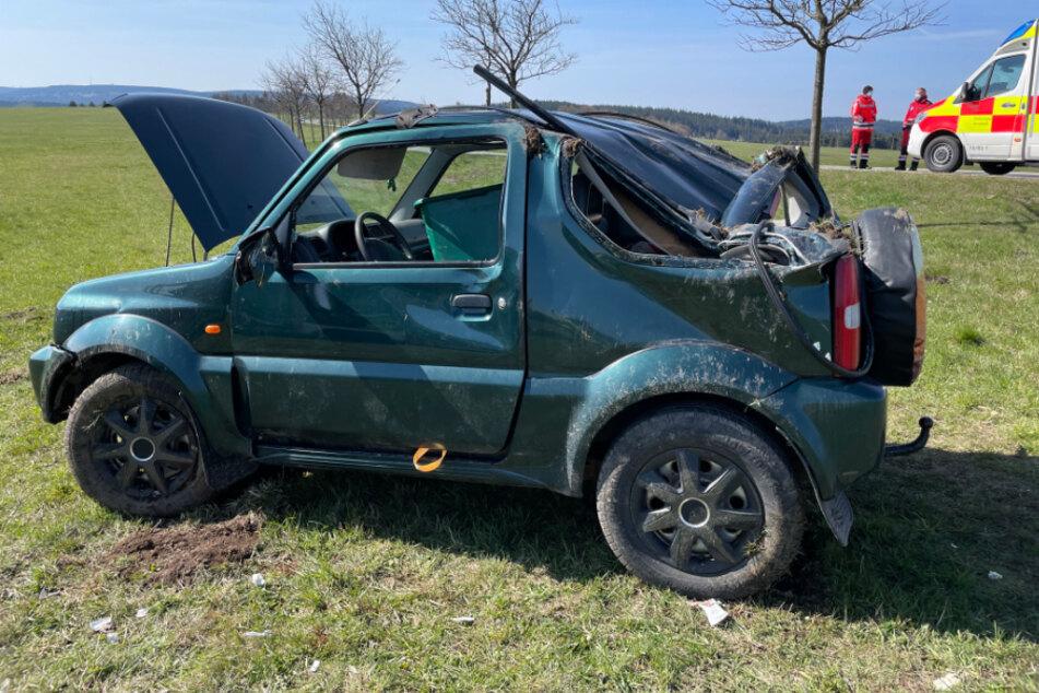 Stark beschädigt steht der verunfallte Jeep auf einem Feld.