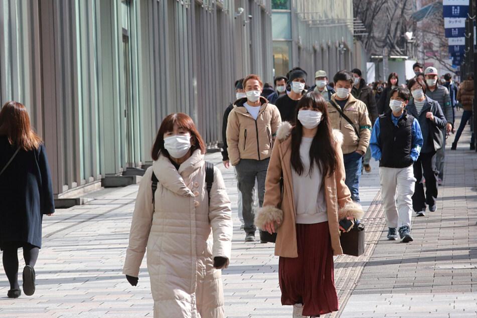 Passanten tragen Schutzmasken und gehen einen Bürgersteig in Tokio entlang.