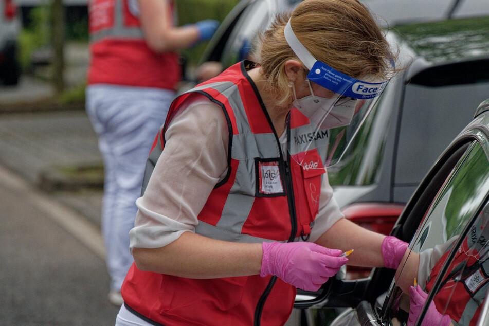 Eine Mitarbeiterin spritzt bei einer Drive-in-Impfaktion eine Corona-Impfung. Trotzdem steigen die Zahlen in NRW besorgniserregend.