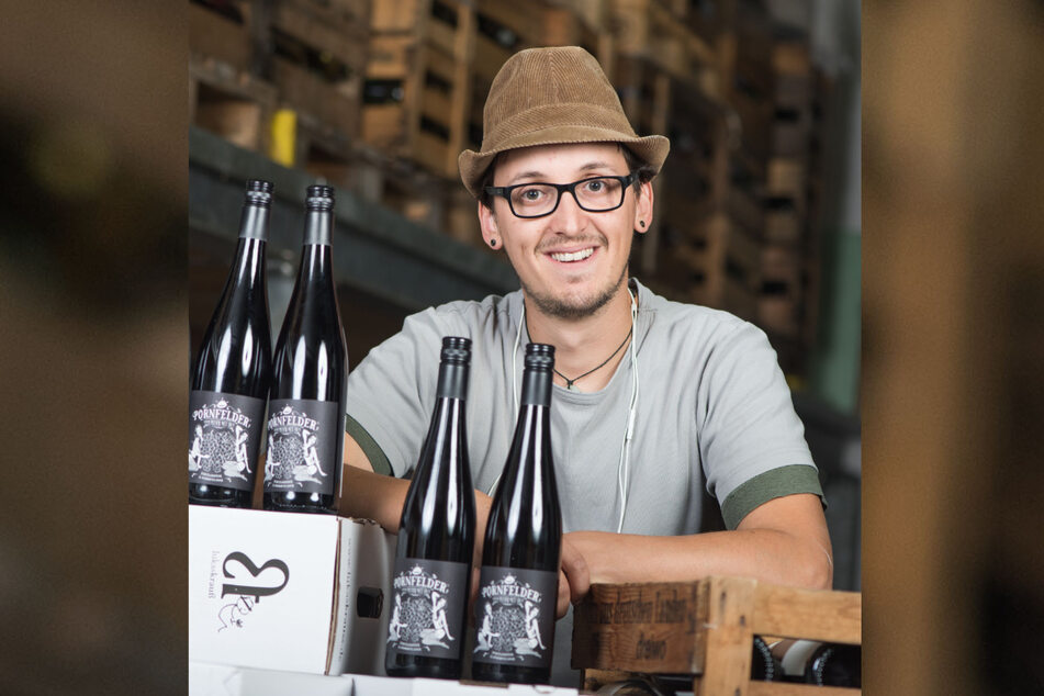 """Winzer Lukas Krauß steht im Weingut in Lambsheim hinter mehreren Weinflaschen der Sorte """"Pornfelder"""". Die Cuvee besteht aus den beiden Rotweinrebsorten Dornfelder und Portugieser."""