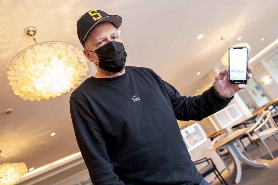 """Rapper Smudo demonstriert auf seinem Smartphone die funktionsweise der App """"Luca""""."""