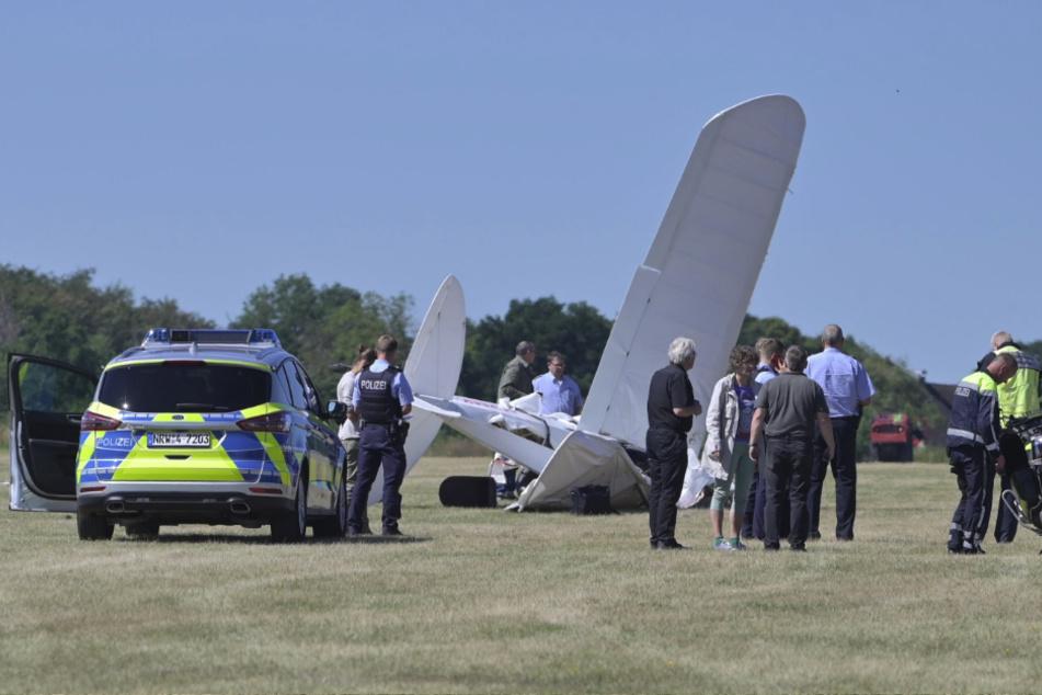 Feuerwehr, Polizei und Rettungsdienst-Mitarbeiter stehen am Flughafen Iserlohn-Rheinermark an der Stelle, an der ein Leichtflugzeug abgestürzt ist.