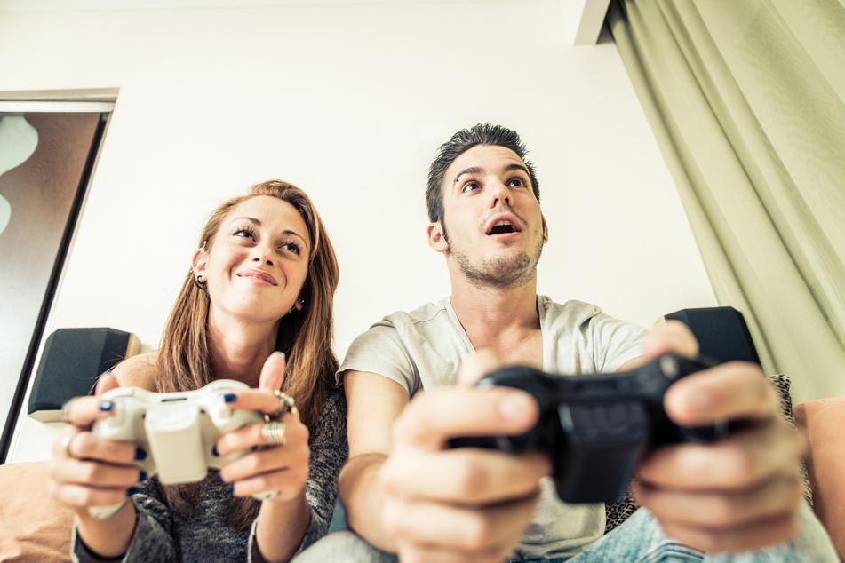 Ein Paar spielt an einer Konsole.