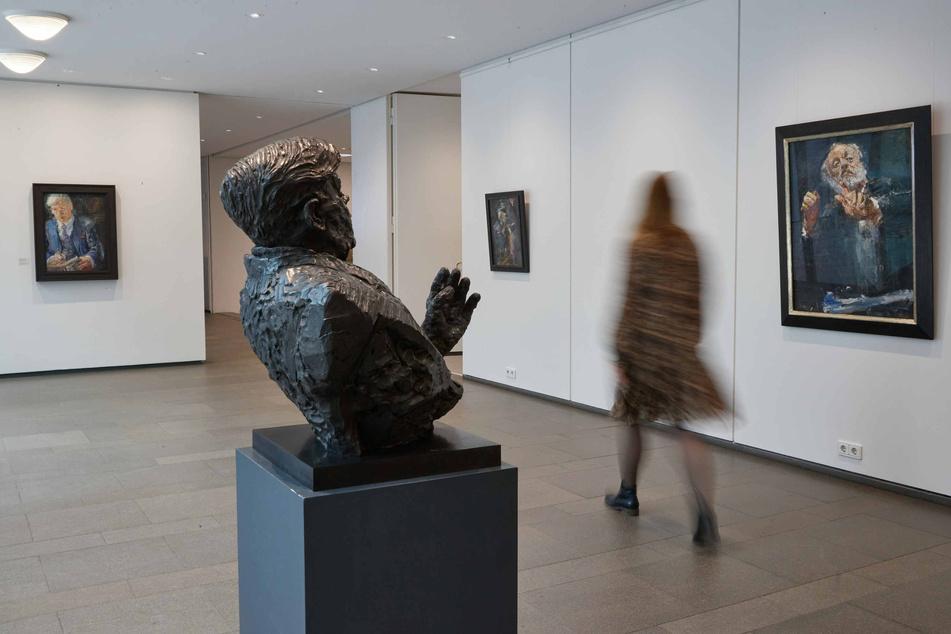 """Eine Journalistin geht durch die Ausstellung """"Kanzlers Kunst - Die Sammlung von Helmut und Loki Schmidt"""" im Ernst Barlach Haus."""
