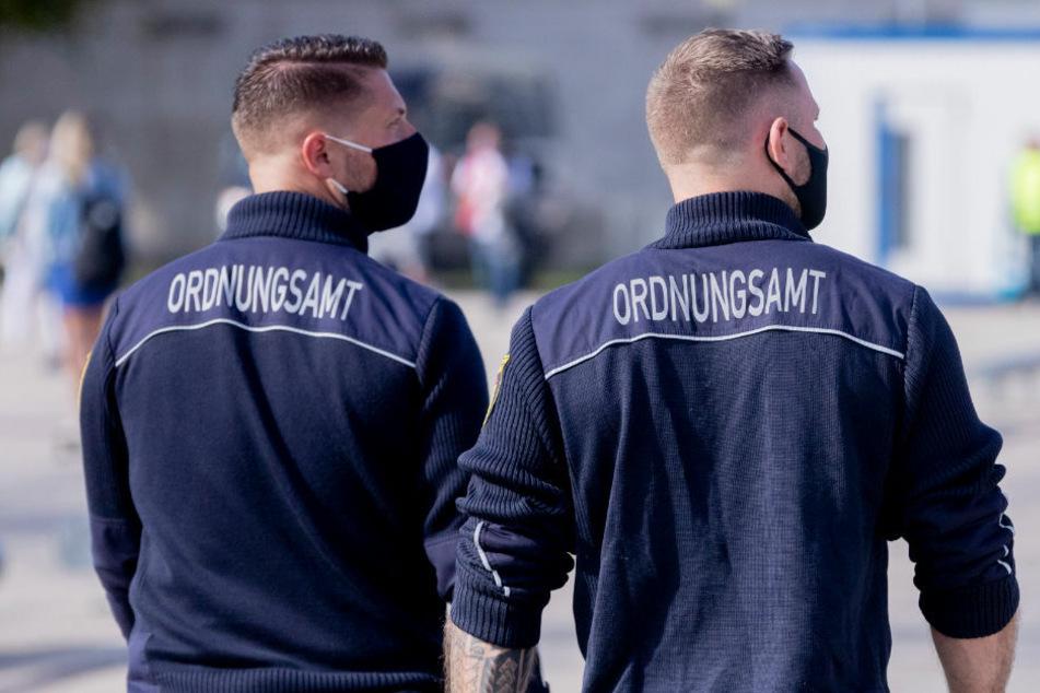 Mitarbeiter des Ordnungsamtes mit Mund-Nasen-Schutz patrouillieren auf dem Stadtplatz Neuer Lustgarten in Potsdam.